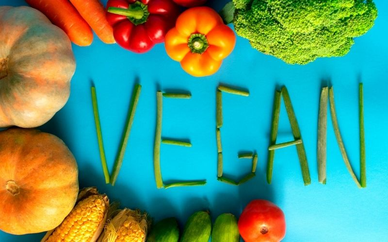 vegan spelled out with plant-based foods like fruits and vegetables